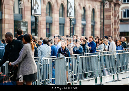 STRASBOURG, FRANCE - SEP, 19 2014: Large crowd in front of Apple Store with customers waiting in line to buy the latest iPhone iPad Apple Watch and notebook - Stock Photo