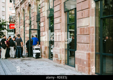 STRASBOURG, FRANCE - SEP, 19 2014: Apple Store with customers waiting in line to buy the latest iPhone iPad Apple Watch and notebook - side view from the street - Stock Photo