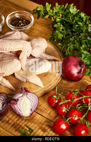 Fresh organic chicken wings on a chopping board with spices and vegetables on old wooden table. - Stock Photo