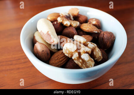 A small white bowl that is full with different types of nuts - Stock Photo