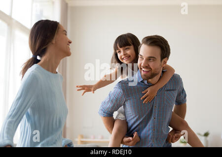 Happy dad piggybacking kid laughing playing catching mom at home - Stock Photo