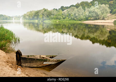 an old wooden boat half submerged in the water on a misty summer morning overlooking the bridge - Stock Photo