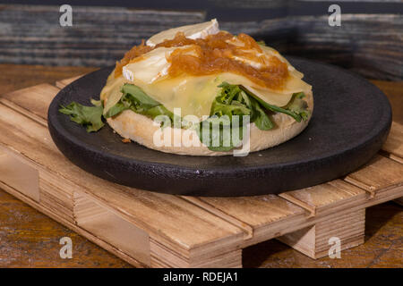 vegan hamburger with cheese and ketchup on black wooden plate - Stock Photo