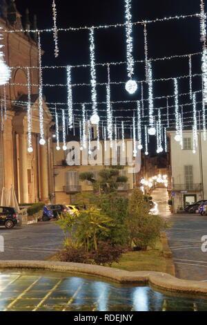 Foto scattata dalla fontana del Nettuno, a sinistra la chiesa di San Francesco. La piazza è illuminata dalle luci di Natale - Stock Photo