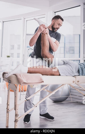 Attentive brunette male person working in clinic - Stock Photo