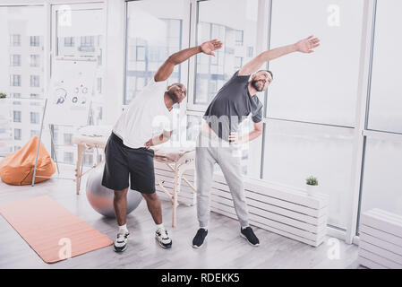 Positive delighted males doing training in gym - Stock Photo