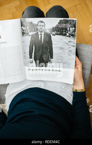 Paris, France - Jan 2, 2019: Vertical image of woman reading article in M le magazine du monde with controversial cover featuring French presidient Emmanuel Macron  - Stock Photo