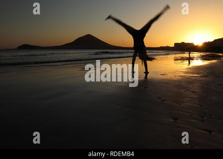 Girl doing gymnastics on a beach at sunset in the Canary Islands - Stock Photo