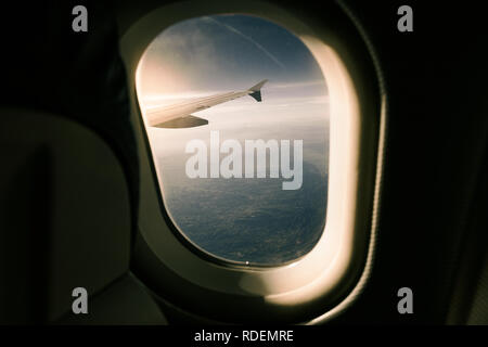 View of sunset from inside the airplane through the window of wing over mountains in Spain - Stock Photo