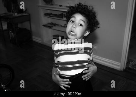 Black and white photo of Hispanic boys making goofy and funny face - Stock Photo