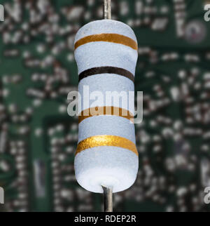 New resistor in front of a Circuit board that shows signs of age and heating - Stock Photo