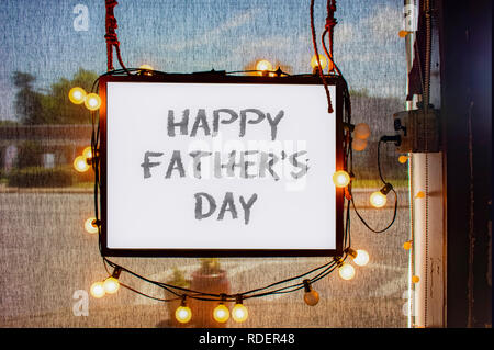 Happy Fathers Day written on hanging sign surrounded by party lights in shop window with semi-transparent dark solar shades behind and dimly viewed ci - Stock Photo