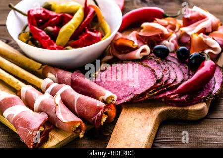 Pepperoni salami slices and bread with prosciutto, italian antipasto, food platter with meat, cold appetizers on wooden table - Stock Photo