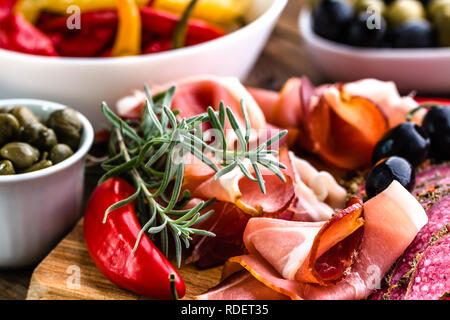 Traditional spanish tapa jamon serrano, or italian antipasto prosciutto, raw ham sliced on wooden board - Stock Photo