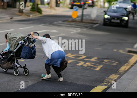 LONDON, UK – May 14, 2018: Woman with child in dangerous situation in crossing busy street. - Stock Photo
