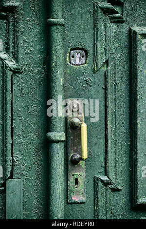 Old wooden carved door painted with green oil paint with bronze handle and steel lock, street design element of typical old European city. - Stock Photo