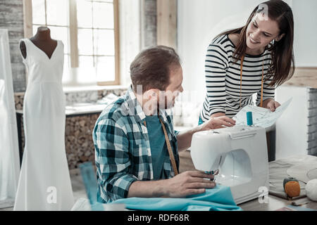 Couple of fashion designers working on sewing bridal dress - Stock Photo
