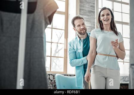 Husband working as fashion designer measuring waistline of wife - Stock Photo
