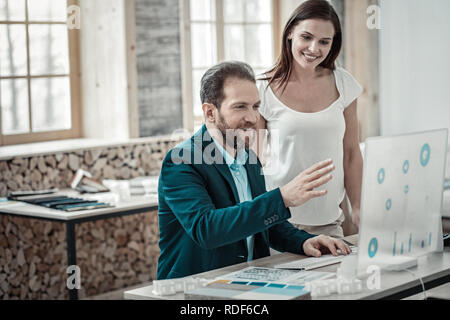 Bearded businessman showing his business plan to wife - Stock Photo