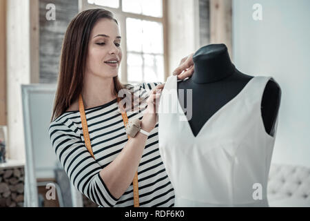 Talented dark-haired woman sewing white long dress - Stock Photo