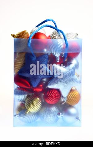 Clear plastic bag filled with Christmas decorations - Stock Photo