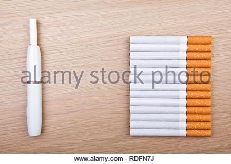 electronic smoke device cigarette wooden table nobody - Stock Photo