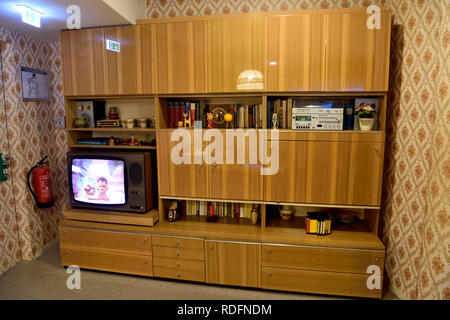 Berlin, Germany - November 10, 2018. Typical Soviet-style cupboard on display at DDR Museum in Berlin, with book, TV and souvenirs. - Stock Photo