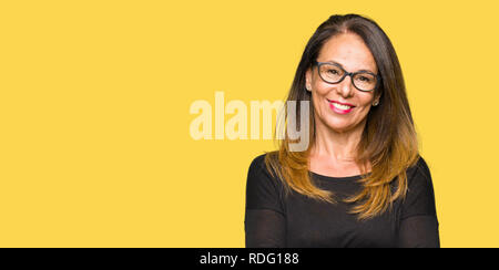 Beautiful middle age woman wearing glasses happy face smiling with crossed arms looking at the camera. Positive person. - Stock Photo