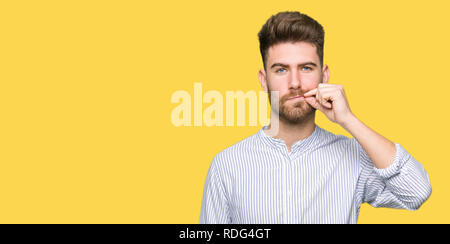 Young handsome man mouth and lips shut as zip with fingers. Secret and silent, taboo talking - Stock Photo