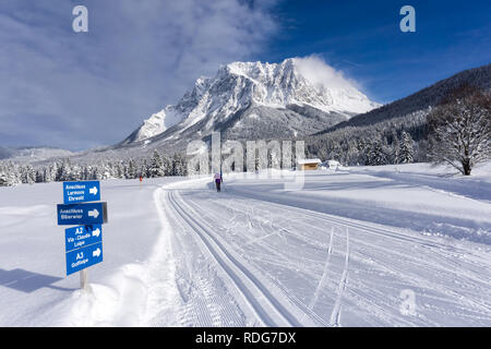 Winter mountain landscape with groomed ski trails and blue sky in sunny day. Ehrwald valley, Tirol, Alps, Austria, Zugspitze Massif  in background. - Stock Photo