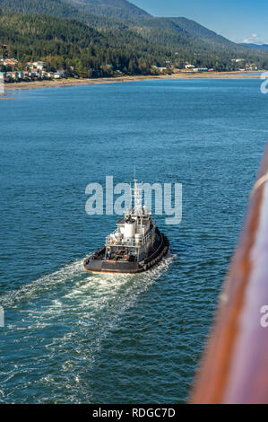 September 14, 2018 - Juneau, Alaska: Tug boat the Taku Wind guiding cruise ship in to port along the Gastineau Channel on a sunny windy day. - Stock Photo