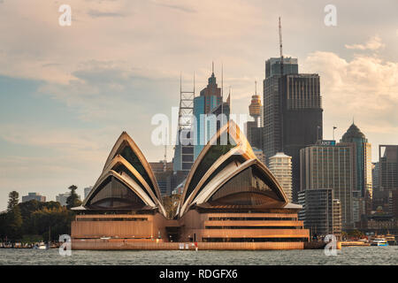 Famous Sydney Opera House in front of the business district. - Stock Photo