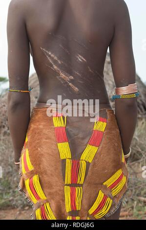 Young Hamar woman with traditional hairstyle with red clay and with scars and marks of being whipped on her back - Stock Photo