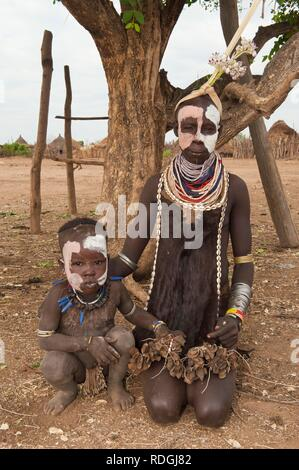 Karo woman with facial paintings, lots of colorful necklaces and cowry shells with her baby, Omo river valley, Southern Ethiopia - Stock Photo