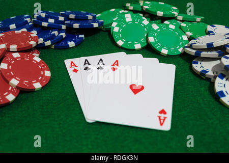 Hand of Poker, four aces and chips  on a felt green background. Perspective view. - Stock Photo