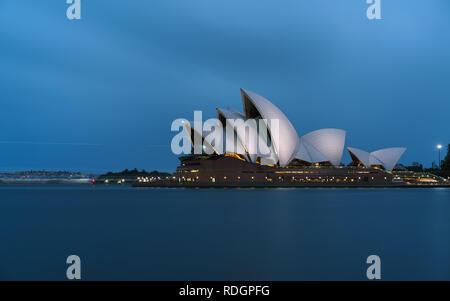 Iconic worlds' buildings - Sydney Opera house in full glory at sunset brightly illuminated - Stock Photo