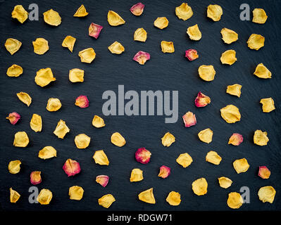 Heart frame made of yellow and red rose petals, on black slate background. - Stock Photo