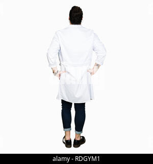 Doctor with long hair wearing medical coat and stethoscope standing backwards looking away with arms on body - Stock Photo