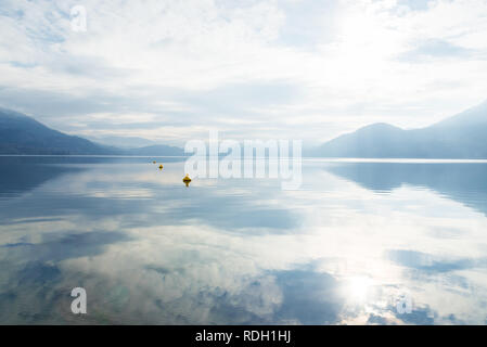 Clouds, fog, sunshine, and mountains reflected in calm lake - Stock Photo