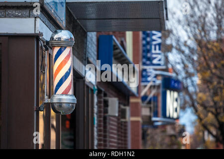 MONTREAL, CANADA - NOVEMBER 6, 2018: Typical American barbers pole seen in front of a barber shop of Montreal, Canada. This pole is a vintage sign ind - Stock Photo