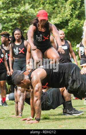 An athletic woman jumps over her male teammates as they compete in the over unders event at Atlanta Field Day on July 14, 2018 in Atlanta, GA. - Stock Photo