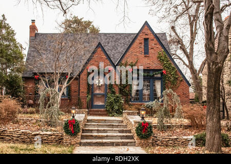 Cute brick cottage with red bows and greenery - decorated for Christmas in bleak wintertime - Stock Photo