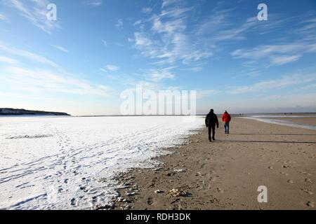 People walking along the snow-covered beach on the East Frisian North Sea island of Spiekeroog, Lower Saxony - Stock Photo