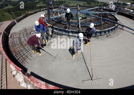 Concreting the foundations during the construction of a wind turbine on a mountain slope in Scholven, Gelsenkirchen - Stock Photo