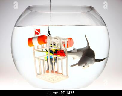 Water toys, scuba diver with an underwater camera in a diving cage next to a shark swimming in a fish bowl, illustration - Stock Photo
