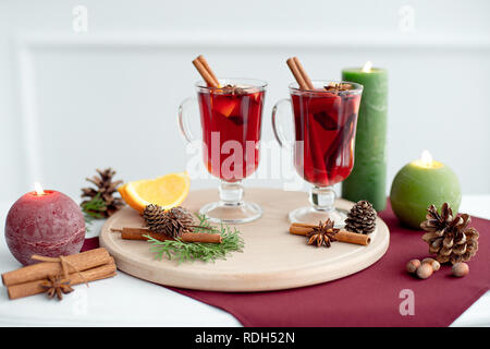 Decorated composition of mulled wine in a glass cup on a white wooden table in a white room - Stock Photo