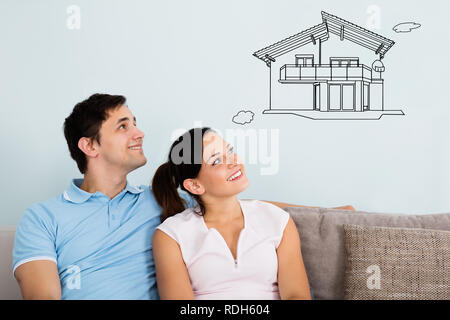 Smiling Young Couple Sitting On Sofa Thinking Of Getting Their New House - Stock Photo
