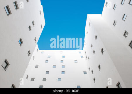 looking up apartment building courtyard - building facade, court and blue sky - Stock Photo