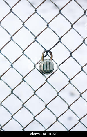 Abstract, desolate image of padlock locked on wire fence in Calgary, Canada, with snow in background . . . prison, jail, crime, weather. - Stock Photo