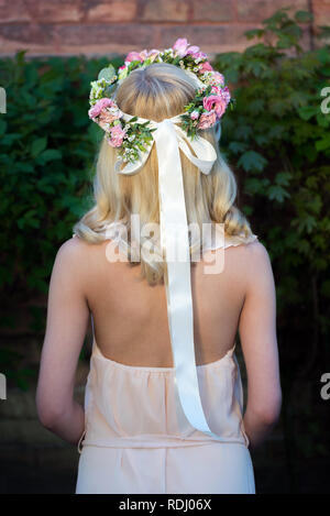 Portrait of a womans back with wreath of flowers on the head. Bride wearing a dress outdoor before the wedding - Stock Photo
